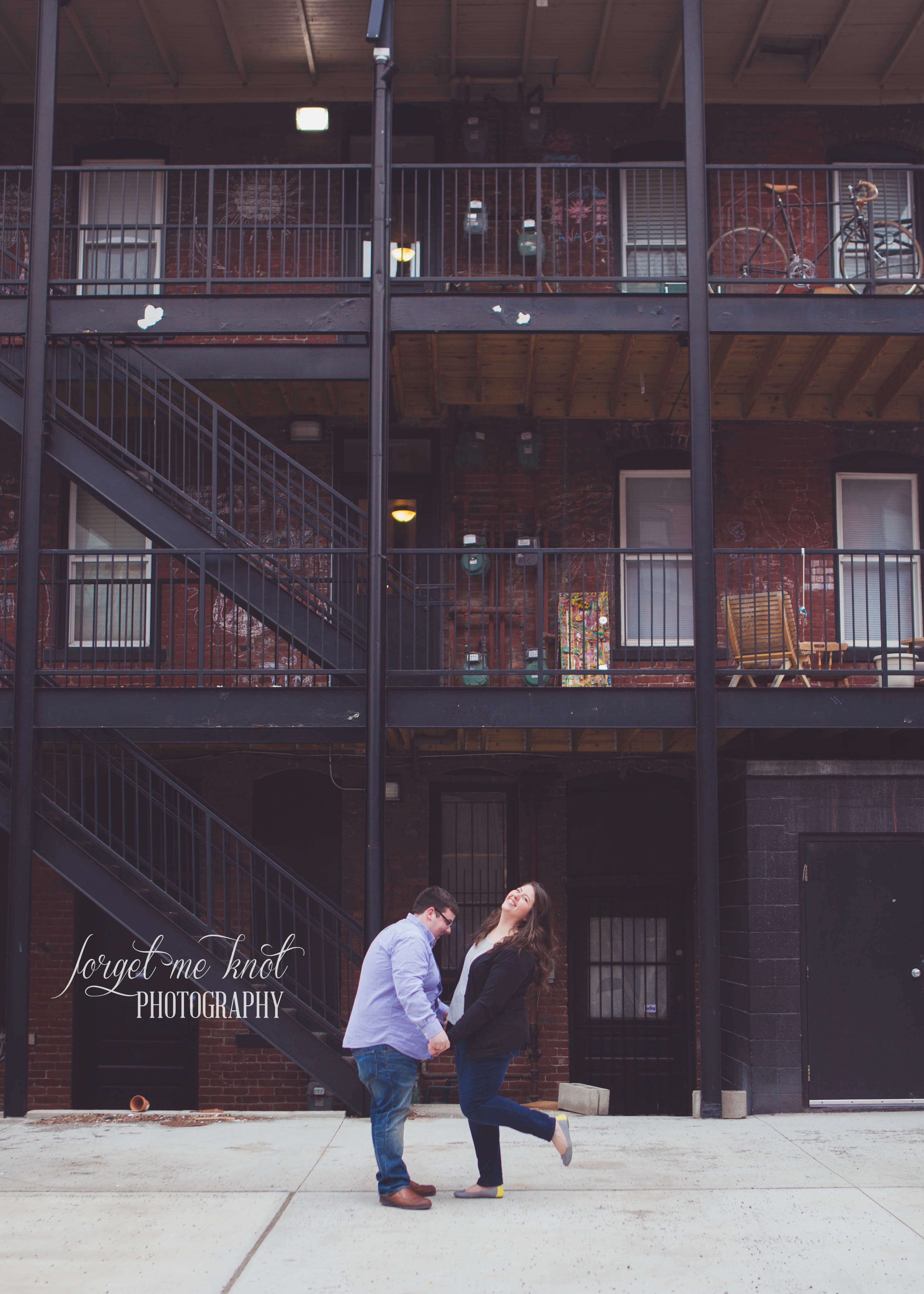 engaged couple laughing in front of stairwell at short north engagement