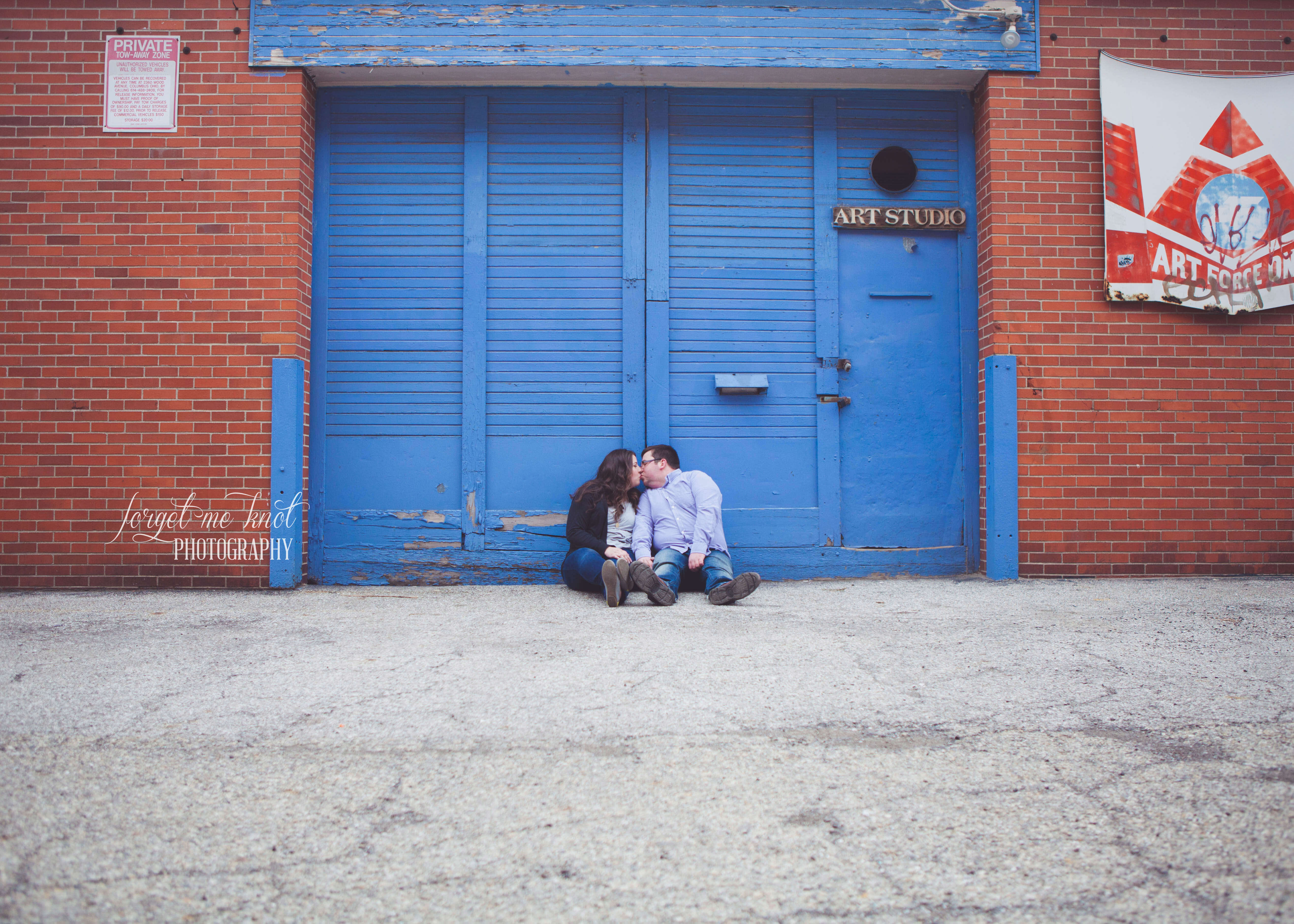 engaged couple kissing in front of blue art studio at short north engagement