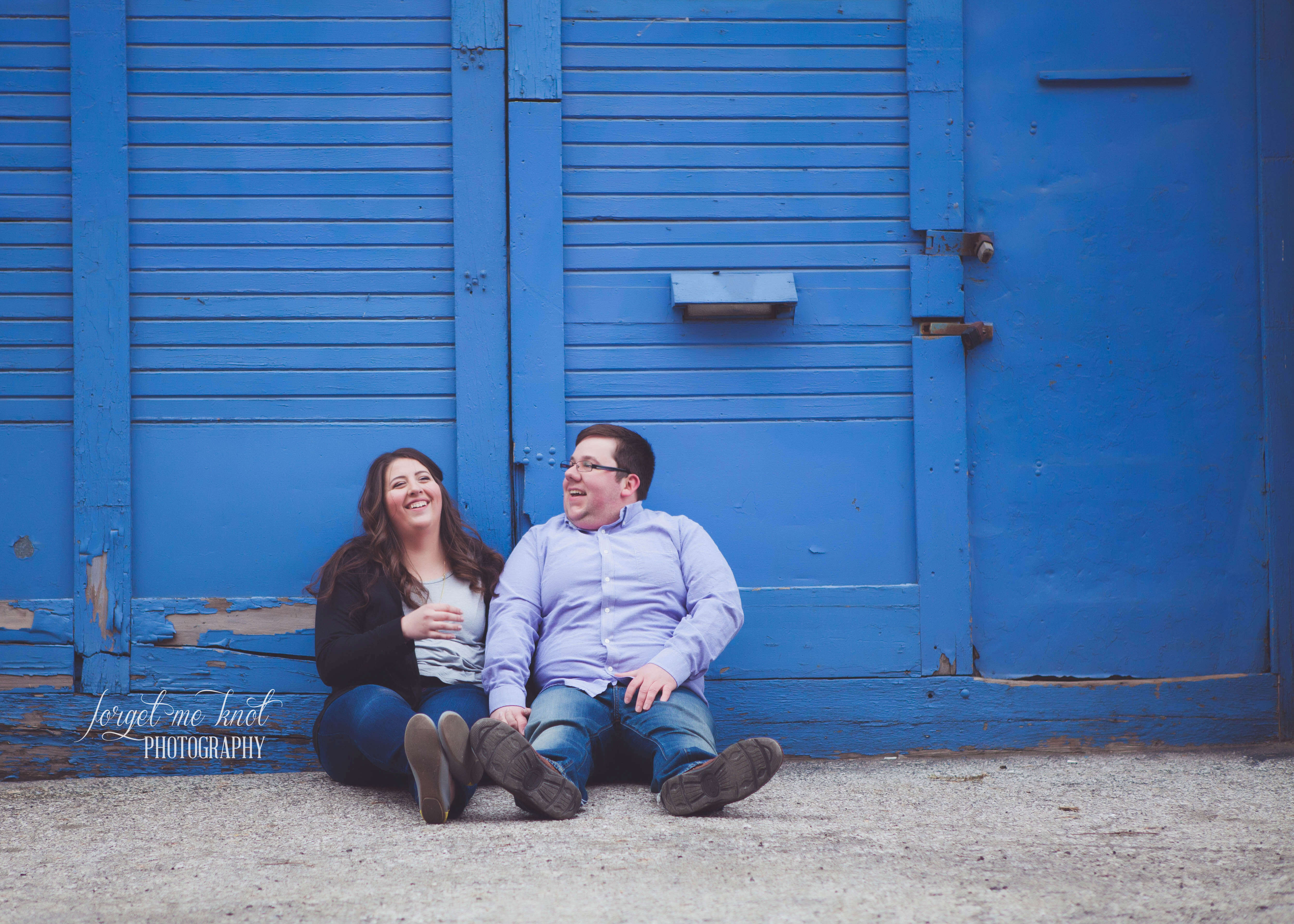 engaged couple laughing while sitting on ground in short north