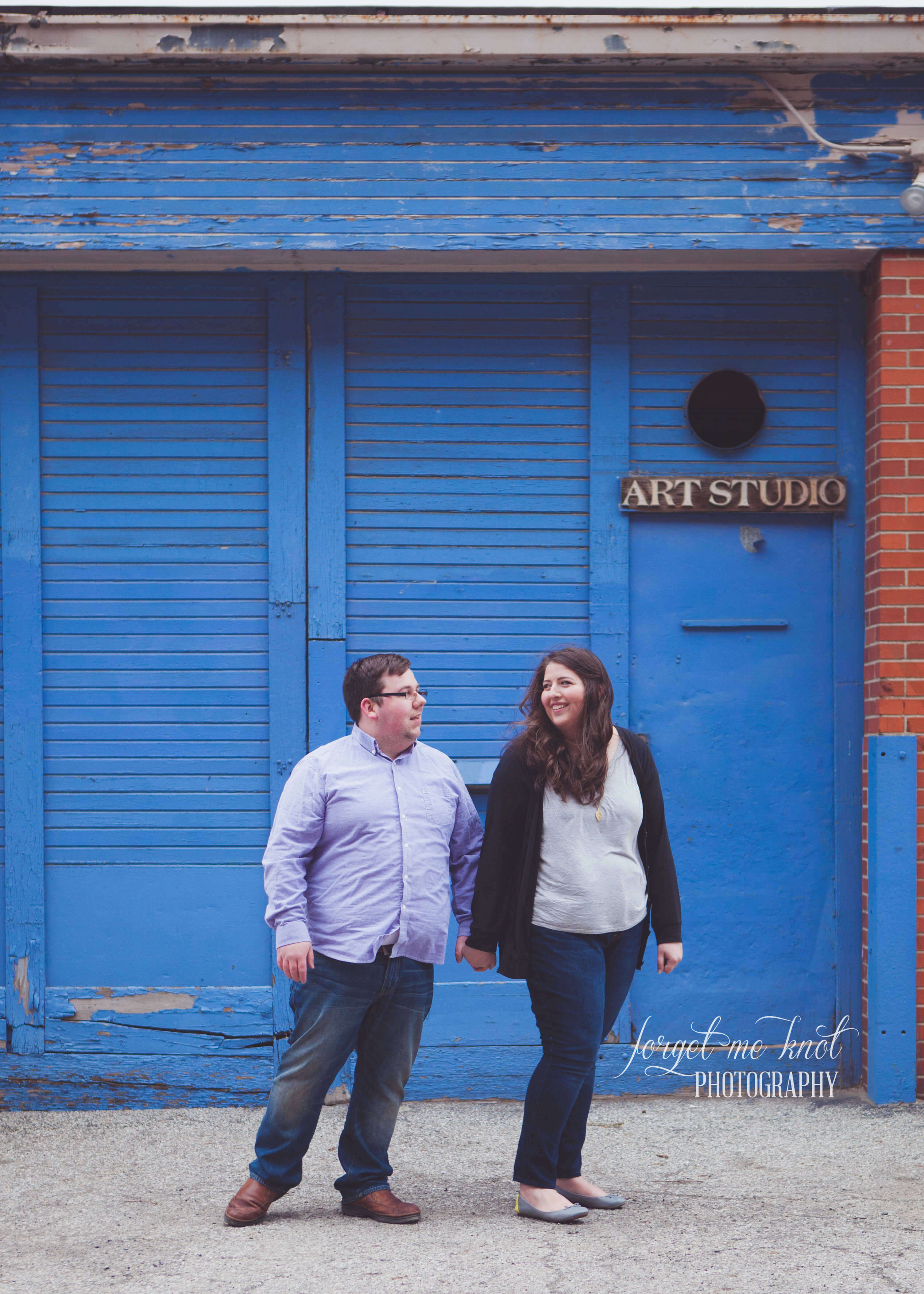 engaged couple holding hands at blue art studio in short north columbus