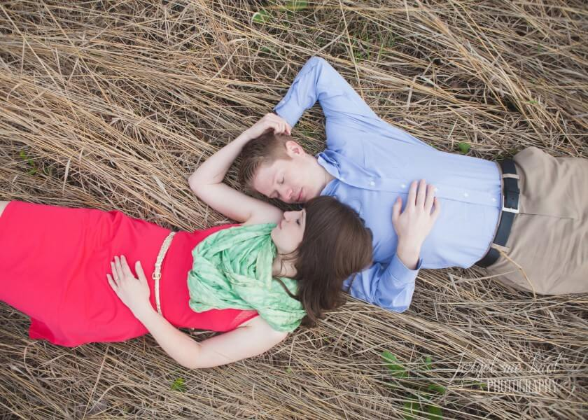 engaged couple laying on back in a field at Columbus Ohio Engagement