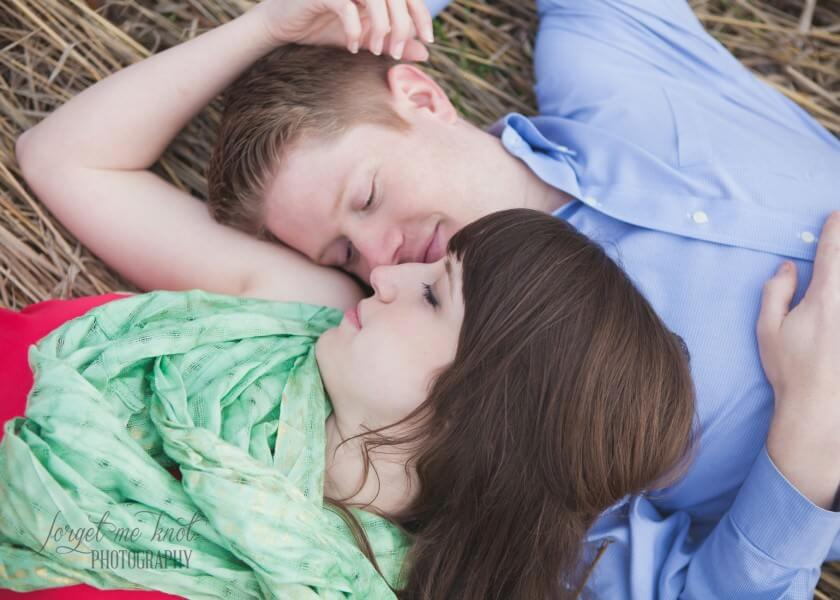 close up of engaged couple in a field laying in grass