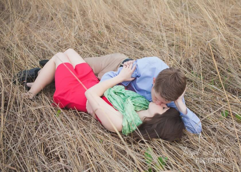 engaged couple kissing while laying in field at Columbus Ohio Engagement