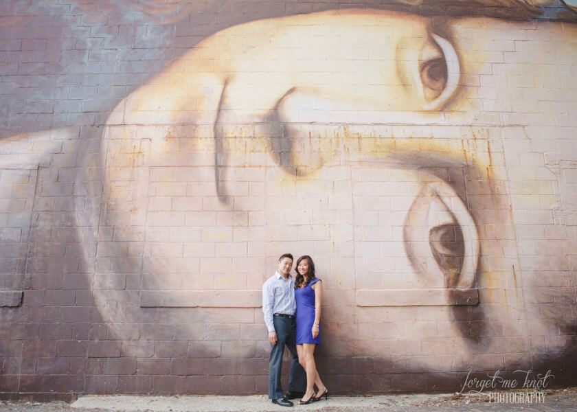 engaged couple in front of mural smiling