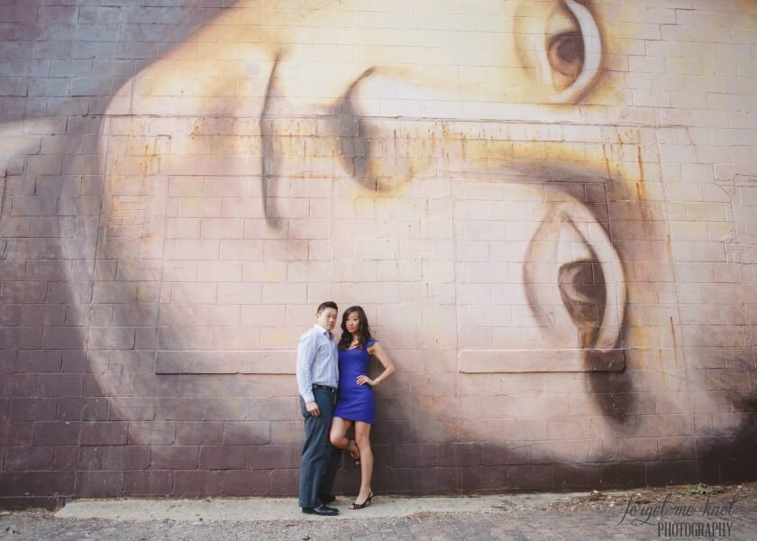 engaged couple leaning on wall mural of mona lisa in columbus ohio