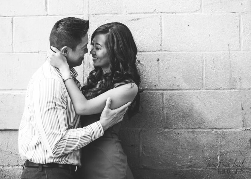 black and white photo of engaged couple going in for a kiss