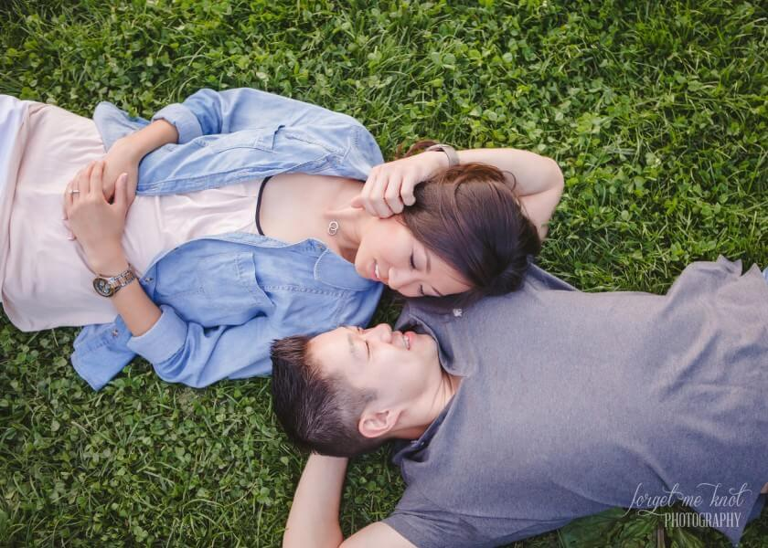 engaged couple hugging while laying in grass
