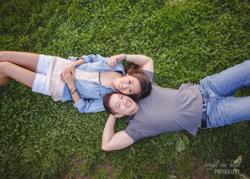 engaged couple laying in grass on backs at columbus ohio photography engagement