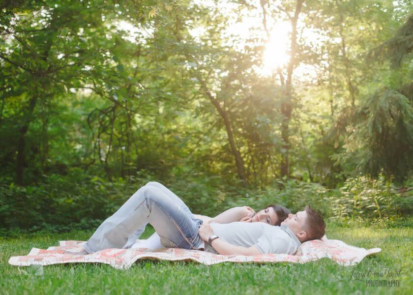 engaged couple laying on quilt for vintage engagement photography session
