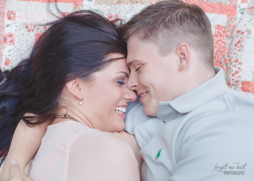 close up of engaged couple cuddling on vintage quilt