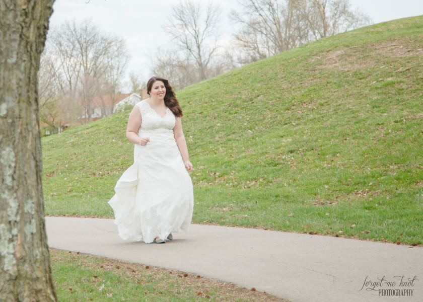 bride holding wedding gown walking to first look