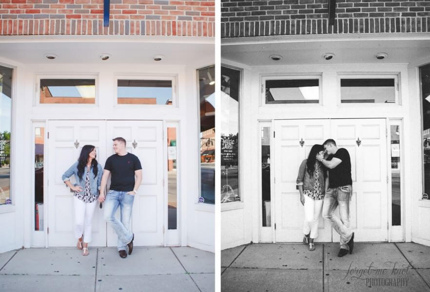 engaged couple looking at each other in front of white and brick building