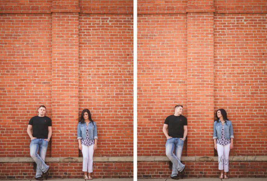 engaged couple looking at each other while on brick wall