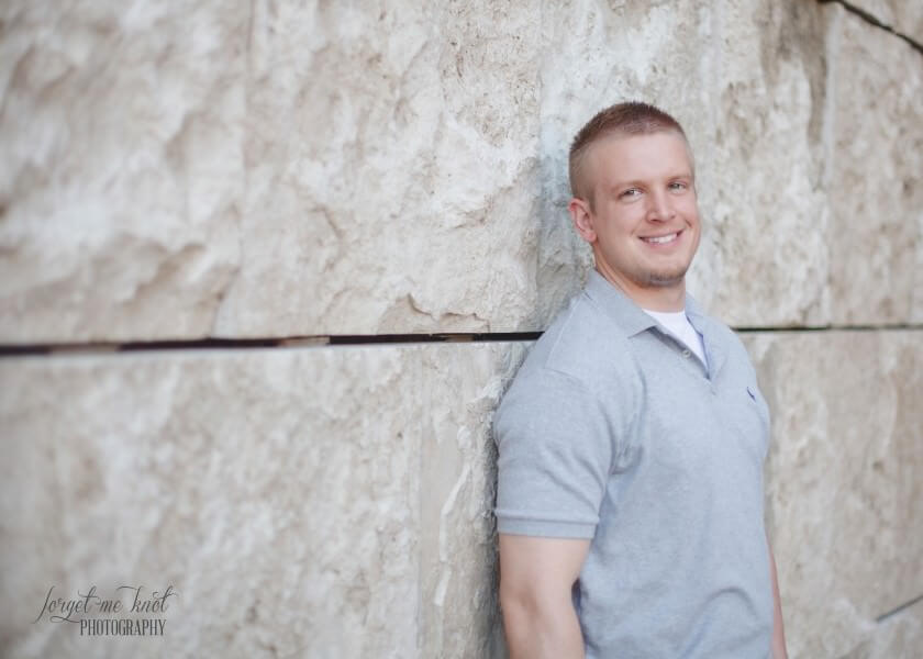 photo of groom to be leaning on wall
