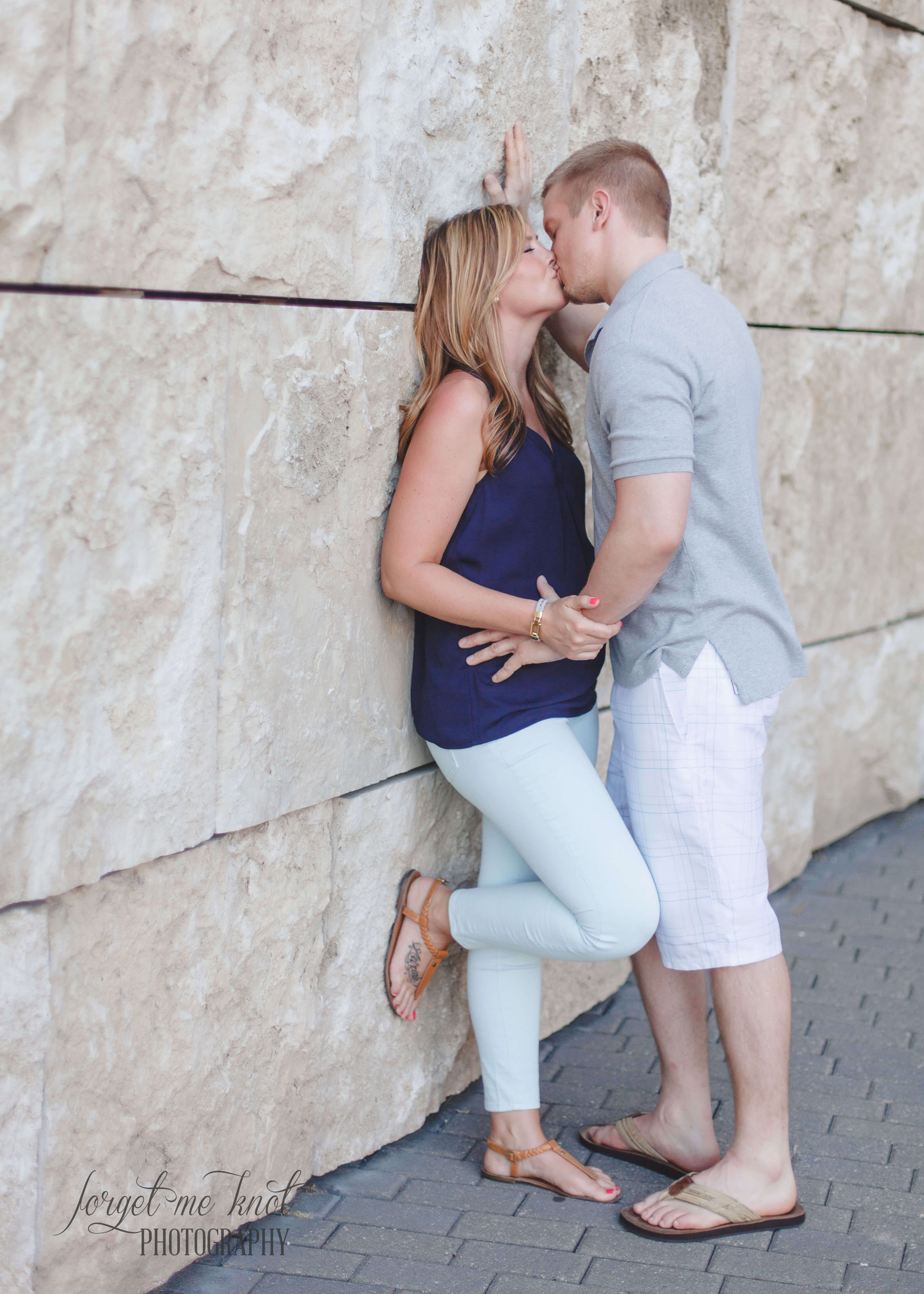 engaged couple kissing along wall at Eden Park Engagement