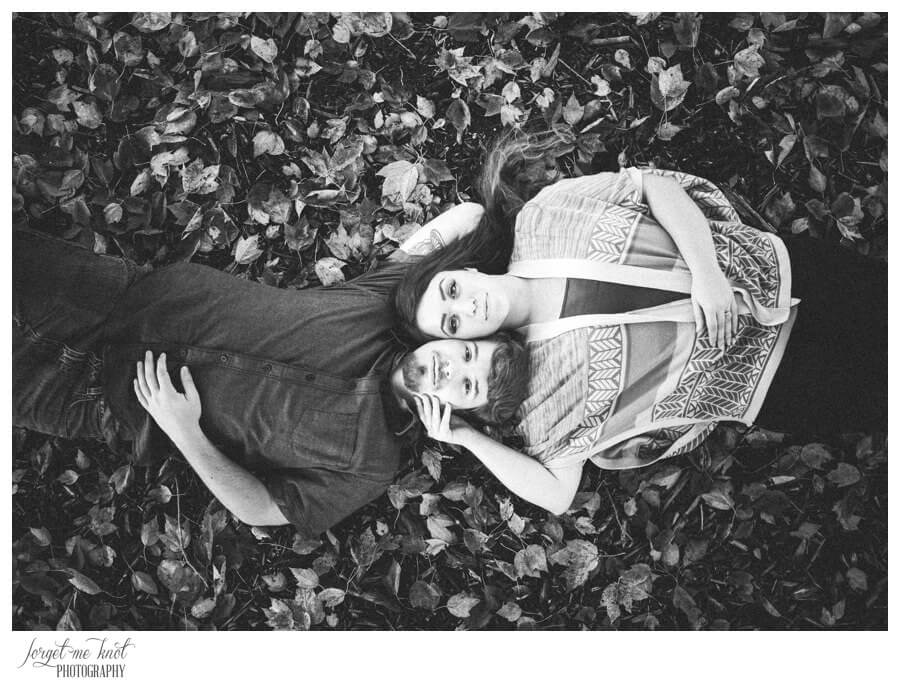 black and white photo of engaged couple laying in leaves at Dawes Arboretum