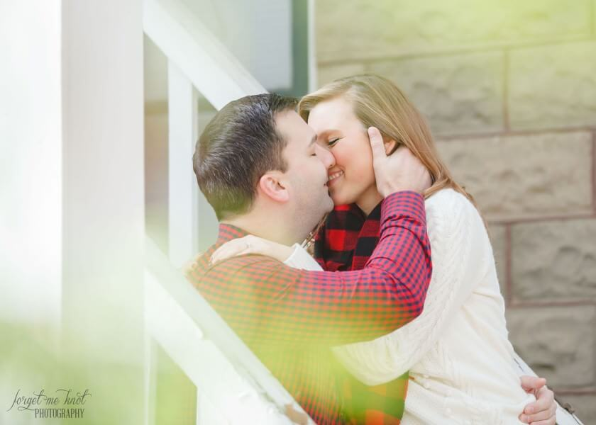 engaged couple kissing while laughing at Bryn Du Mansion