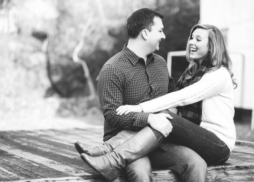 black and white photo of engaged couple sitting together