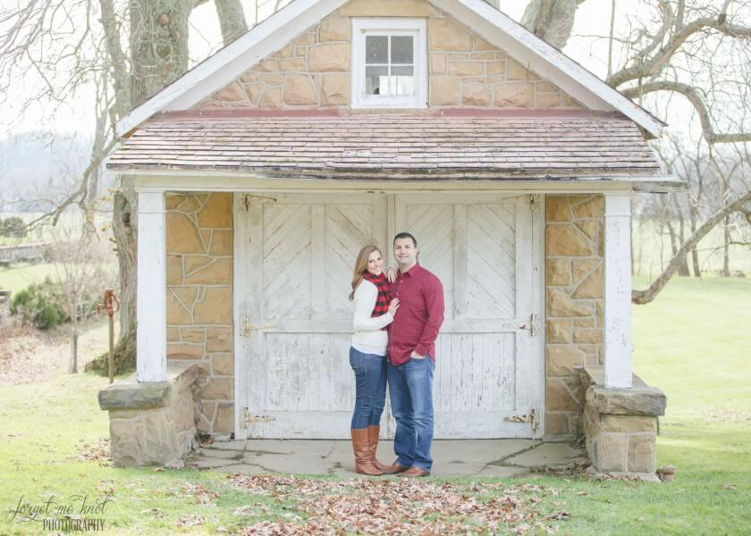 engaged couple in front of small building