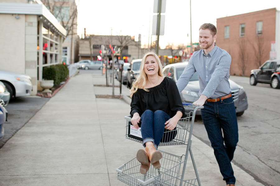 engagement photo of couple spinning in grocery cart