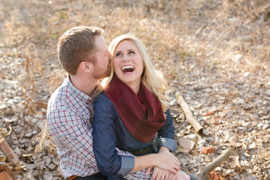 engagement photo of couple laughing and sharing secrets