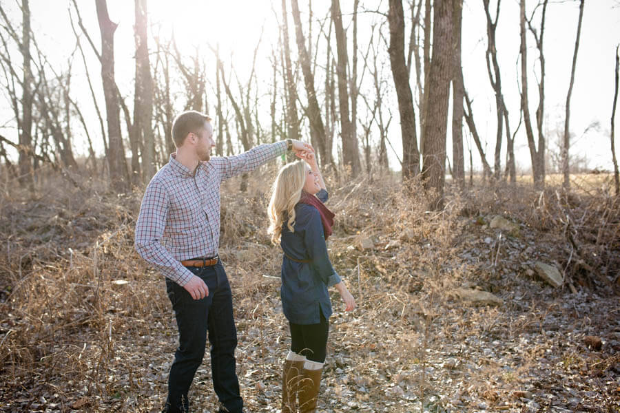 engagement photo of couple twirling in winter trees