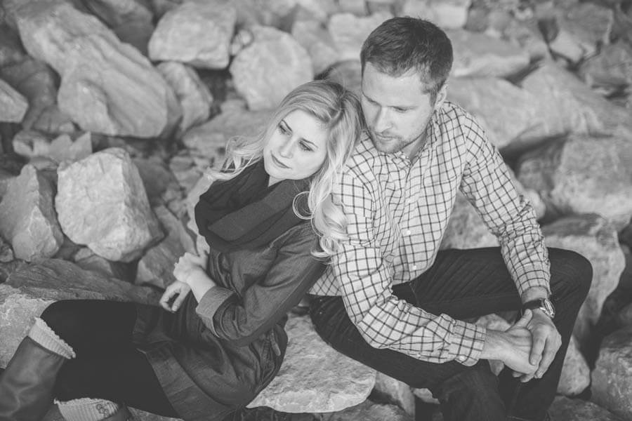 engagement photo of couple under overpass cuddling