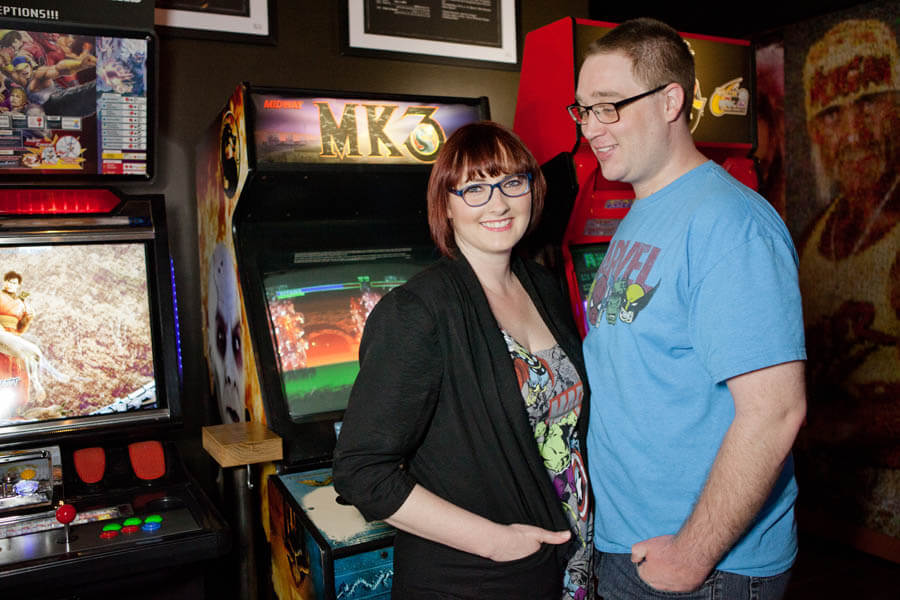 engagement photo of couple at arcade
