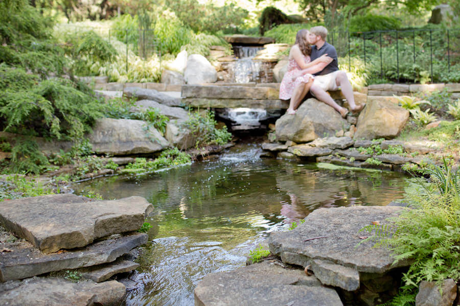 engaged couple kissing in background at Inniswood Metro Gardens