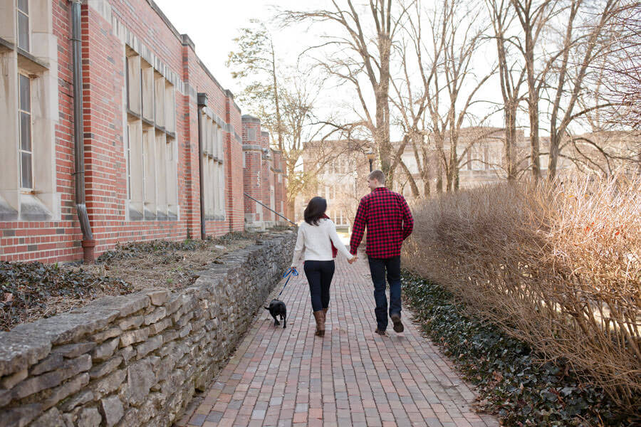 engagement photo of couple walking their dog at Ohio State University mirror lake