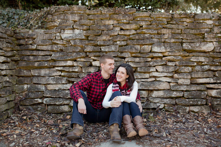 engagement photo of couple sitting and laughing at mirror lake