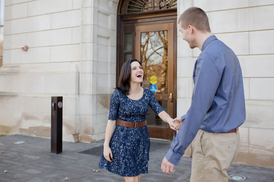 engagement photo of couple walking holding hands at Ohio State University library