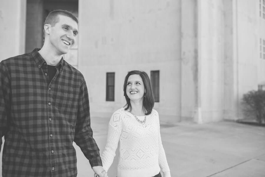 engagement photo of couple walking and laughing at Ohio State University stadium