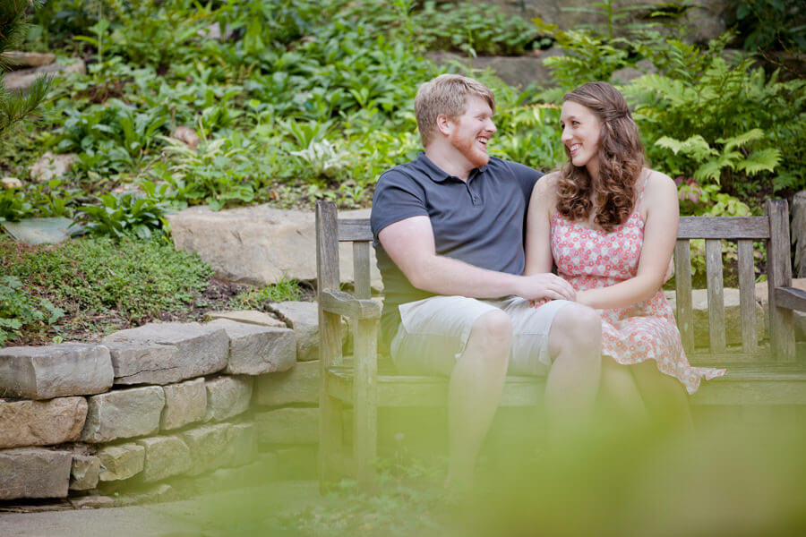 engagement photo of couple laughing while sitting on bench at Inniswood Metro Park