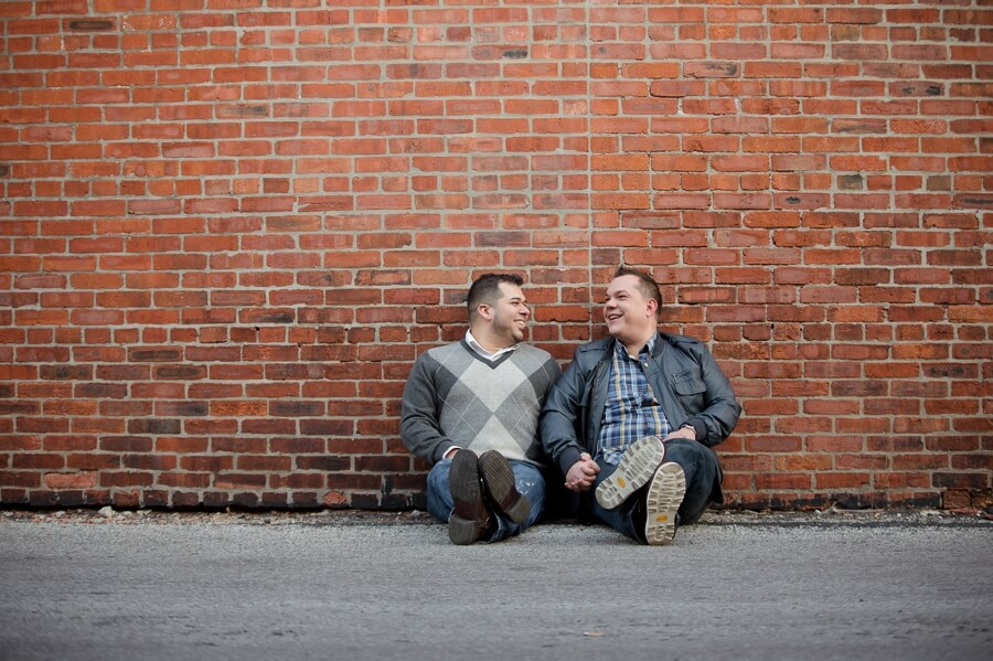 same sex couple sitting on brick wall in columbus ohio short north