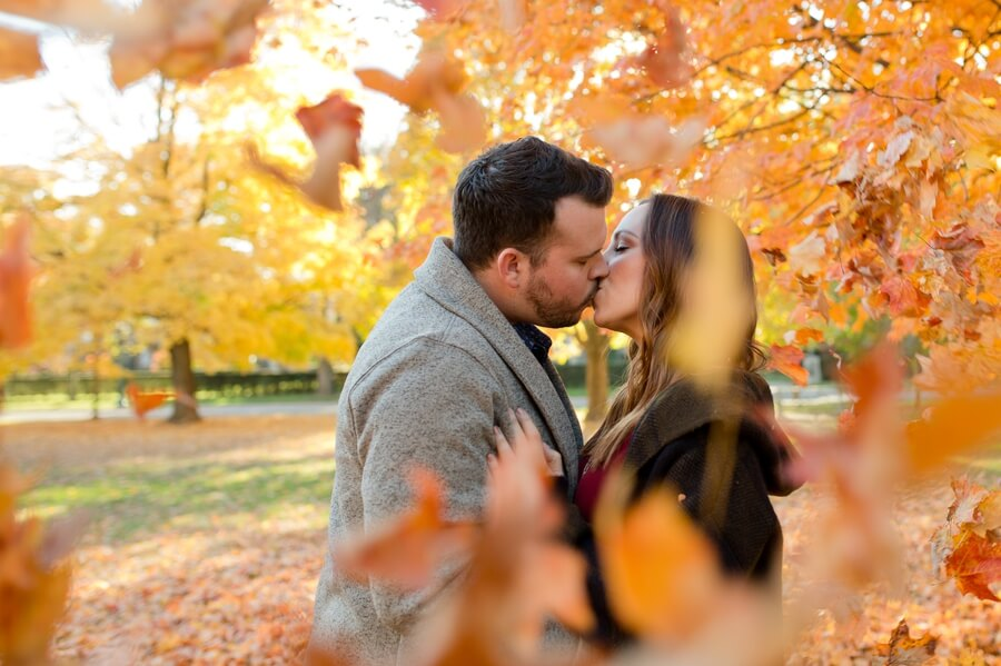 engaged couple kissing under falling leaves