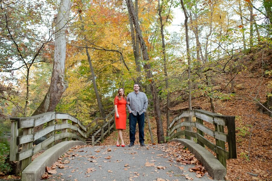 engaged couple walking on bridge at park