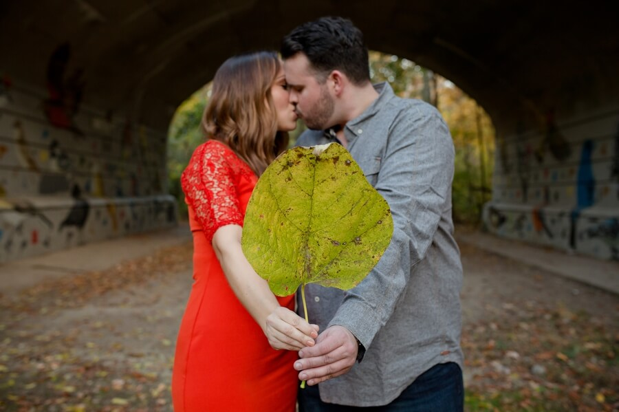 couple kissing behind a leaf