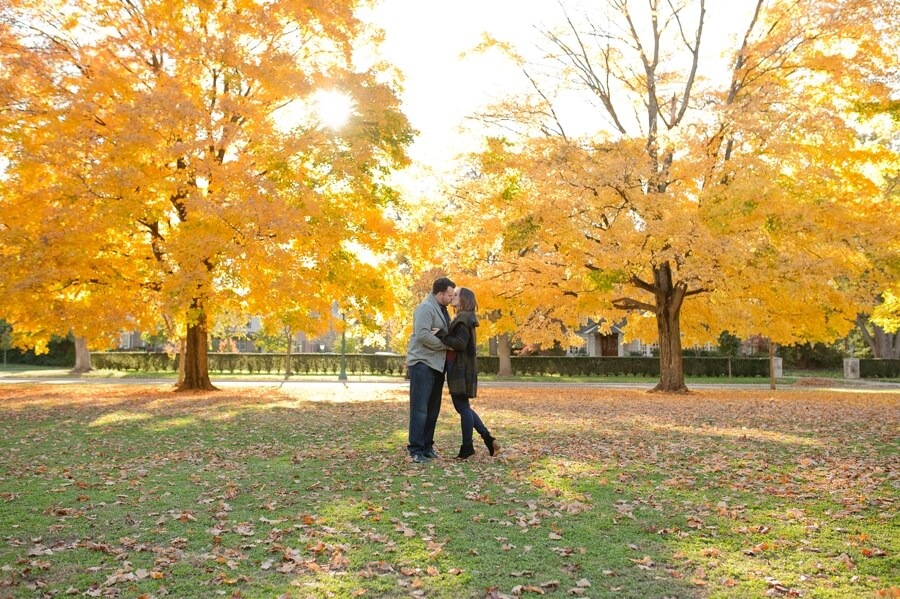 engaged couple kissing in middle of park