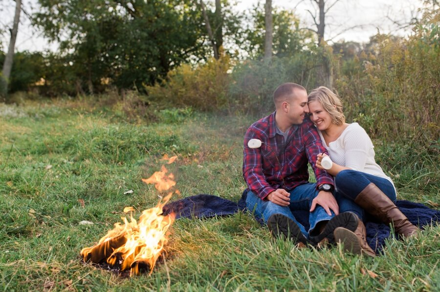 engaged couple cuddling by bonfire at farm