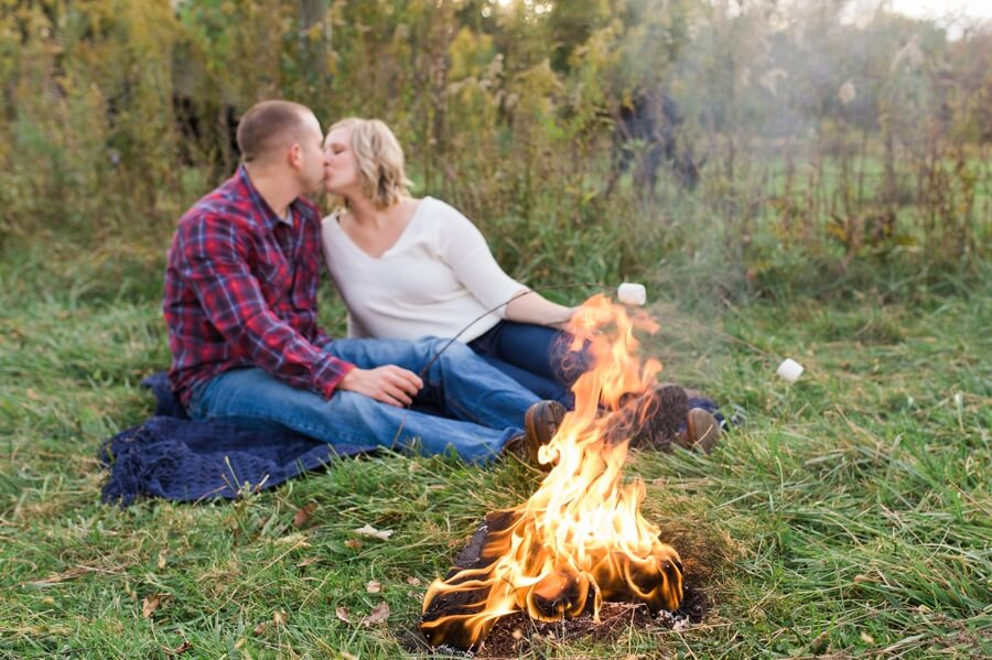 engaged couple kissing at bonfire at columbus farm