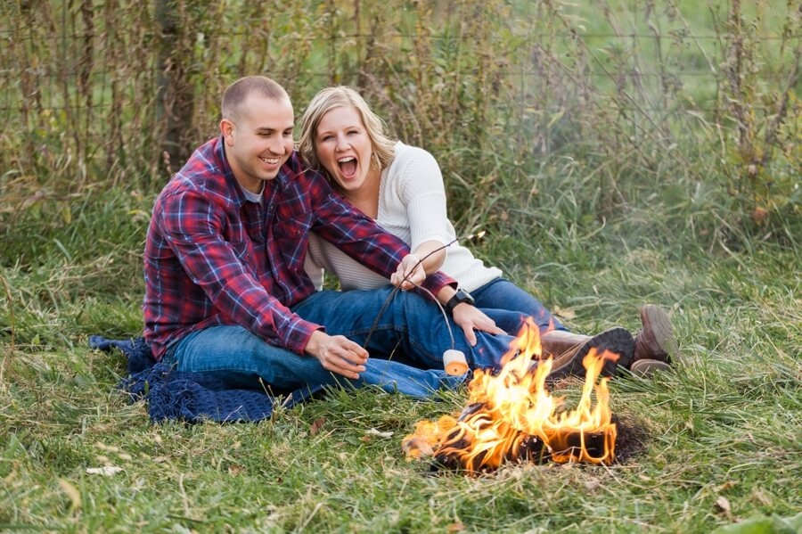 engaged couple laughing and roasting marshmallows at columbus ohio farm