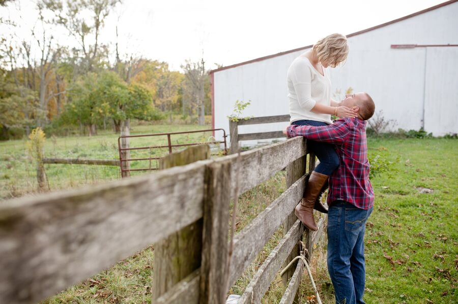 engaged couple on fence at columbus ohio farm