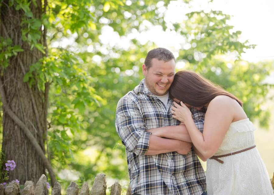 engaged couple giggling on bridge at Irongate Equestrian Center