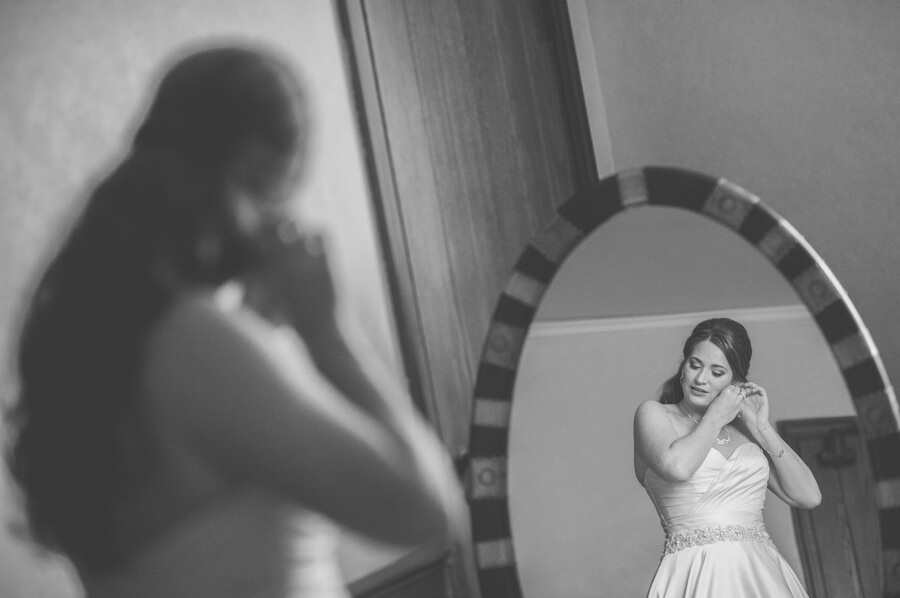bride putting on earrings through mirror