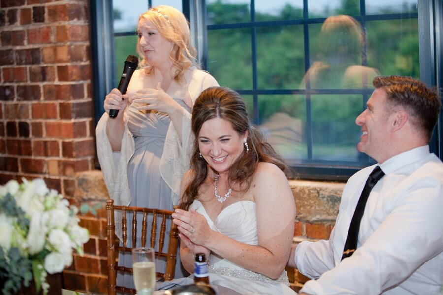 bride laughing at wedding party speech
