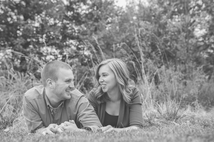 engaged couple laying in grass at Highbanks Metro Park