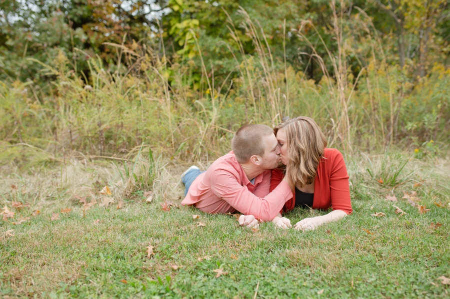 engaged couple kissing in grass at Highbanks Metro Park