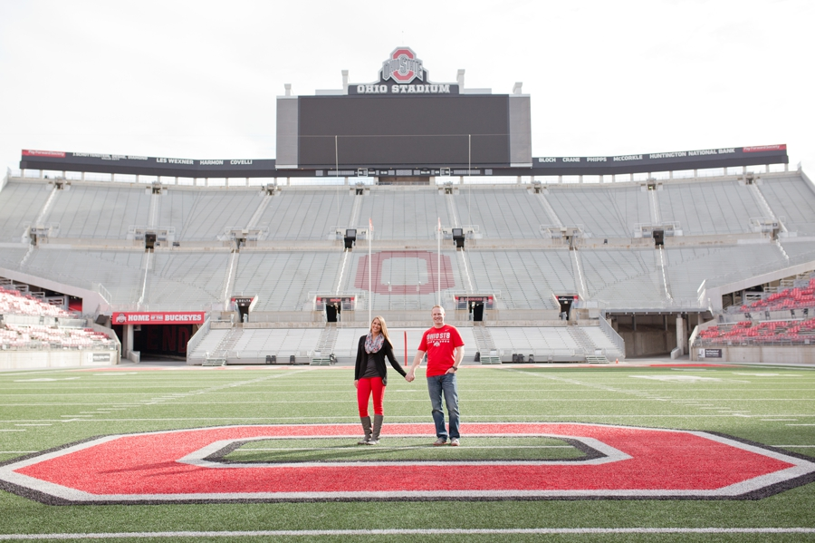 engaged couple holding hands in middle of Ohio State University stadium