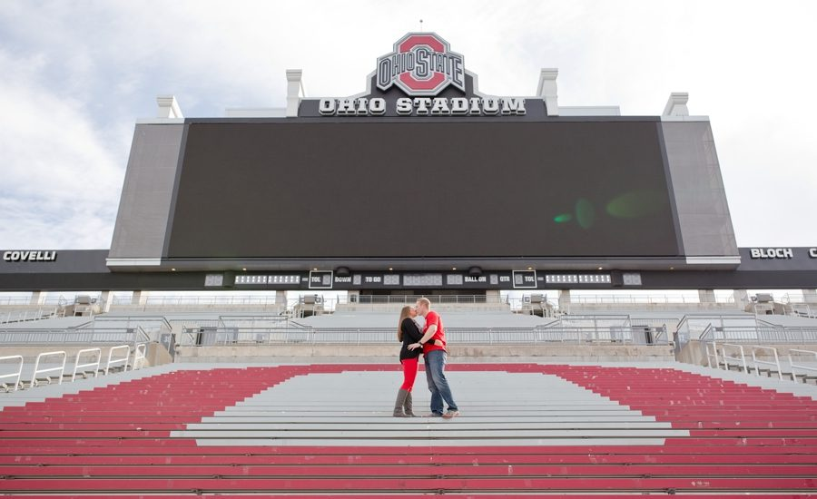 engaged couple kissing at Ohio State University stadium